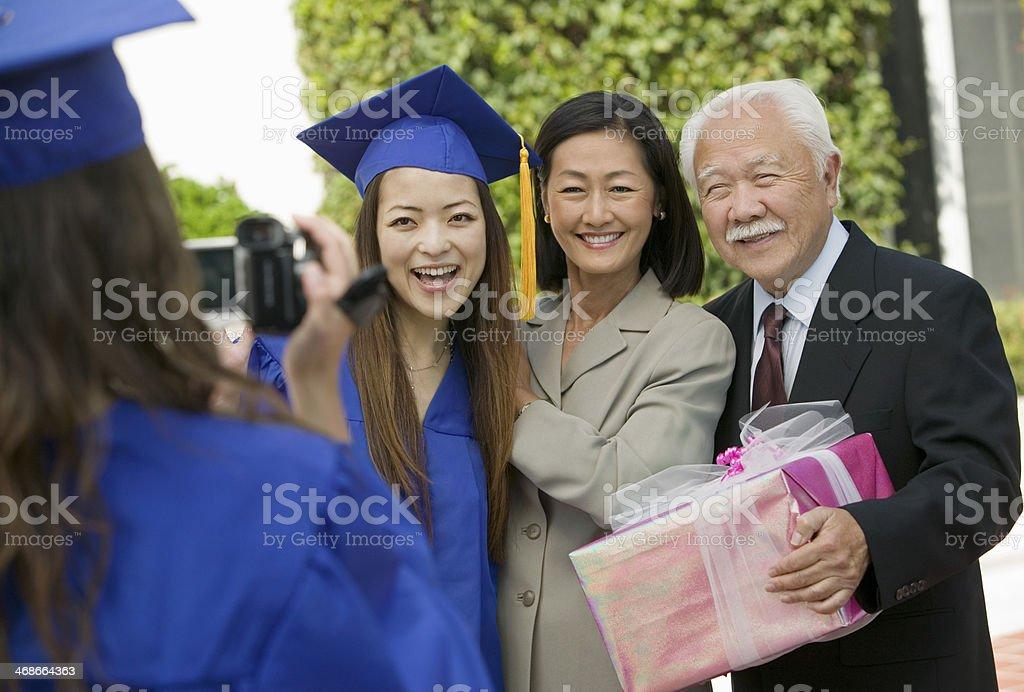Family member videotaping graduation celebration stock photo