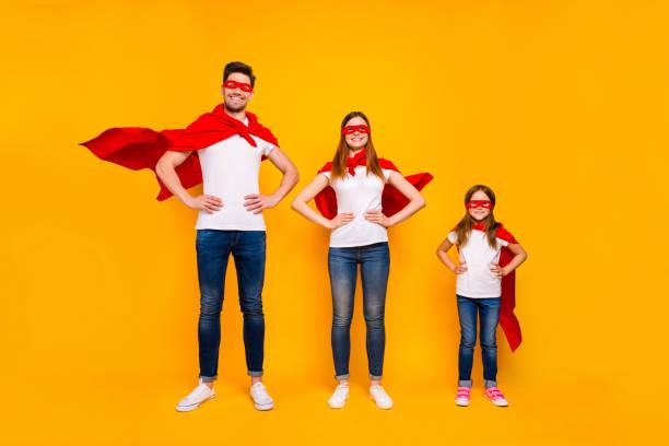 familjemedlemmar som spelar tecknade otroliga karaktärer bär superhjälte flygande rockar isolerad gul bakgrund - superwoman barn bildbanksfoton och bilder