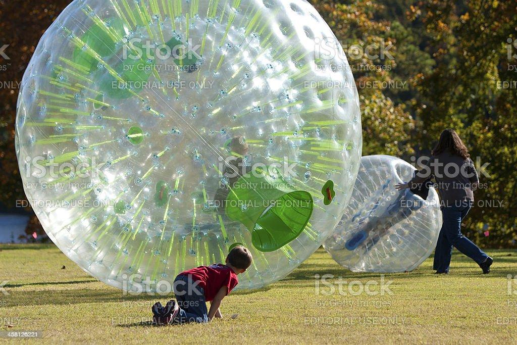Family Members Push Kids In Plastic Balls royalty-free stock photo