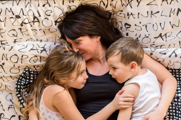Familie. Mutter, Tochter und Sohn im Bett liegend – Foto