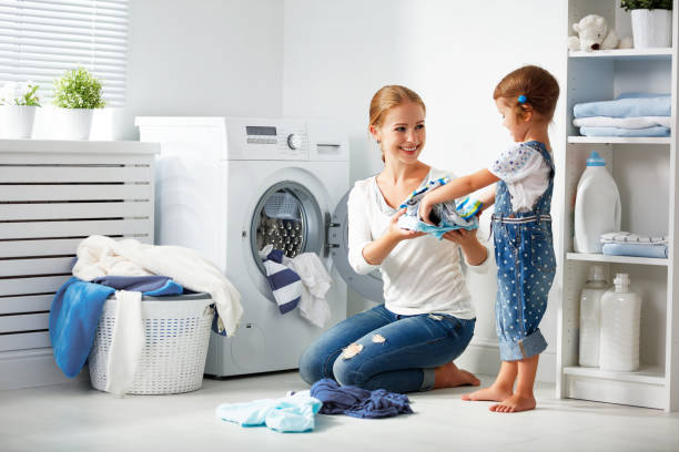 family mother and child girl  in laundry room near washing machine stock photo