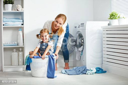 istock family mother and child girl  in laundry room near washing machine 670137374