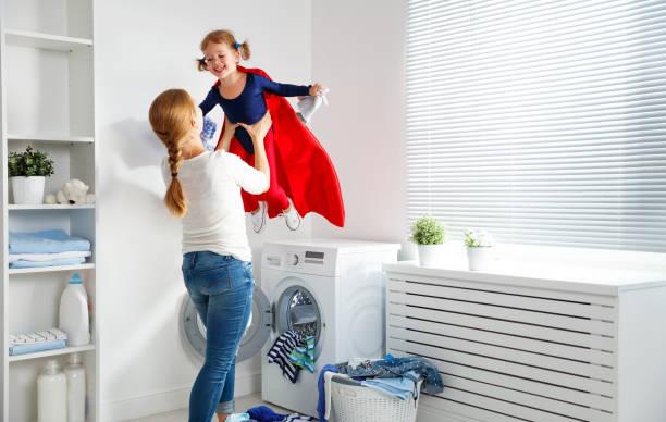 family mother and child girl little superhero helper in laundry - baby super hero imagens e fotografias de stock
