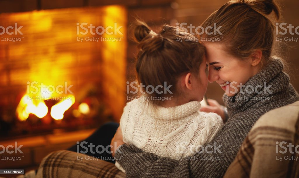 family mother and child hugs and laughing on winter evening by fireplace stock photo