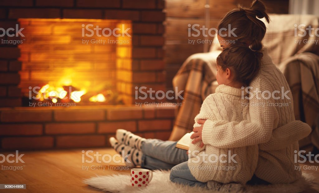 family mother and child daughter hugs and warm on winter evening by...