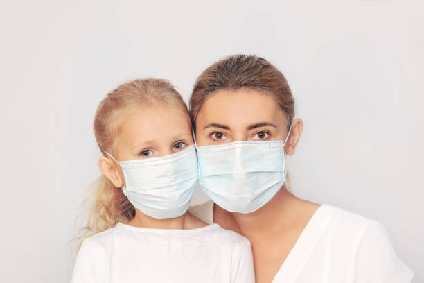 Family mother and daughter in medical masks together on an isolated background stock photo