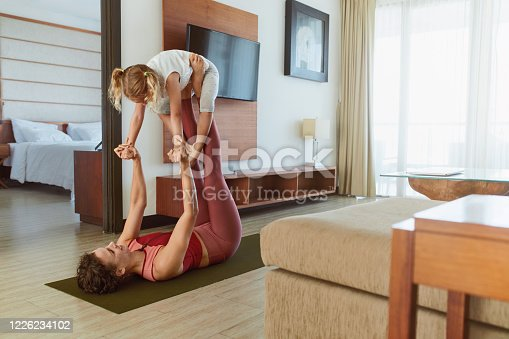 916126642 istock photo Family. Mother And Daughter Practicing Partner Yoga At Home. Young Woman And Kid Exercising Together. Sporty Parent And Child Doing Acroyoga In Living Room. 1226234102