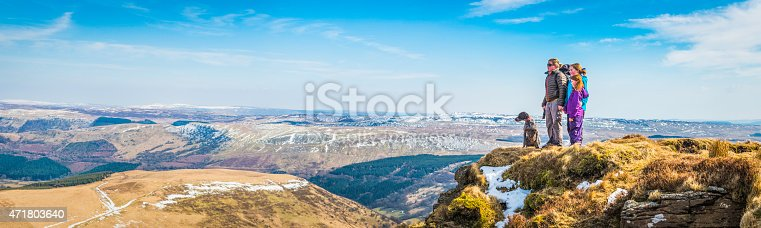 Family group of mother and two daughters hiking with their dog stood on mountain top looking out over wild outdoors landscape to the distant horizon. ProPhoto RGB profile for maximum color fidelity and gamut.