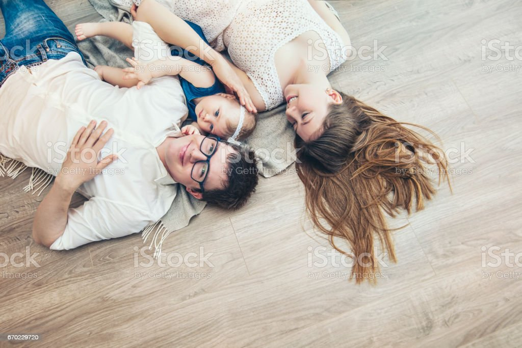 Family mother father and baby are happy together at home smiling stock photo
