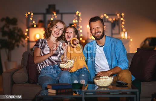 family mother father and child daughter watching projector, TV, movies with popcorn in the evening   at home
