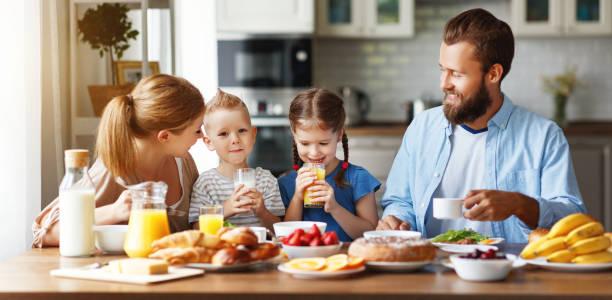 padre de madre de familia y los niños tienen desayuno en la cocina por la mañana - desayuno fotografías e imágenes de stock