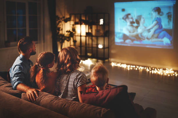 family mother father and children watching projector, TV, movies with popcorn in   evening   at home family mother father and children watching projector, TV, movies with popcorn in the evening   at home dusk stock pictures, royalty-free photos & images