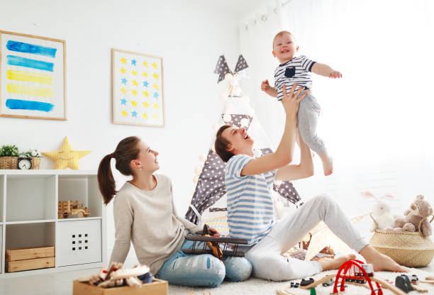 family mother father and   son playing together in children's playroom stock photo