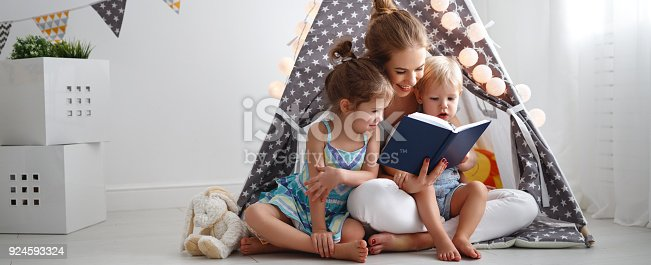 istock family mother reading to children book in tent at home 924593324