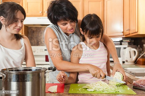 istock Family, mother with two daughters, cook meatballs. 472196697