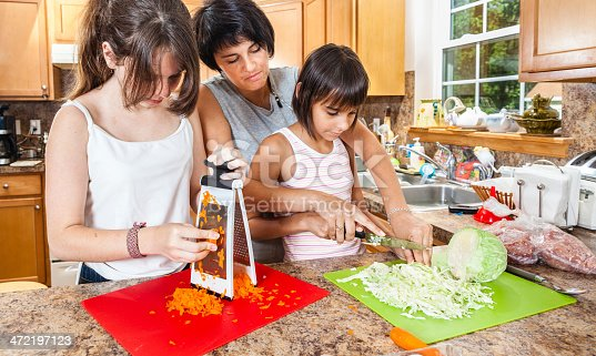 istock Family, mother with two daughters, cutting vegetables for salad 472197123