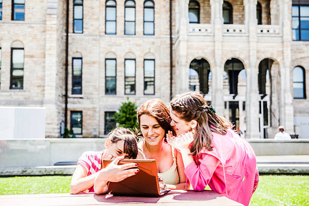 family, mother with two daughters, reading info at the laptop - scranton pa stock photos and pictures