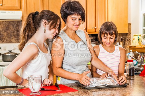 istock Family, mother with two teenagers daughters, cook together 472200199