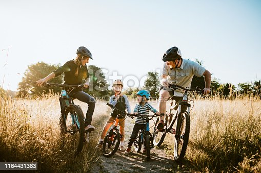 A father and mother ride mountain bikes together with their two small children.  A fun way to spend time together and exercise while on vacation in the Seattle, Washington area.