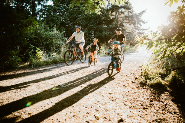 Family Mountain Bike Riding Together on Sunny Day A father and mother ride mountain bikes together with their two small children.  A fun way to spend time together and exercise while on vacation in the Seattle, Washington area. leisure equipment stock pictures, royalty-free photos & images
