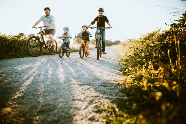 family mountain bike riding together on sunny day - aktywny tryb życia zdjęcia i obrazy z banku zdjęć