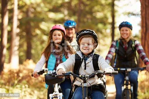 istock Family mountain biking on forest trail, front view, close-up 518185202