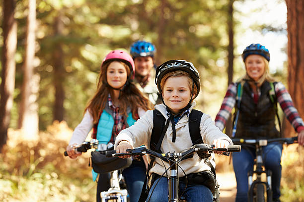 Family mountain biking on forest trail, front view, close-up Family mountain biking on forest trail, front view, close-up leisure equipment stock pictures, royalty-free photos & images