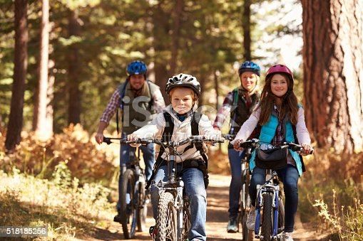 istock Family mountain biking on forest trail, front view 518185256