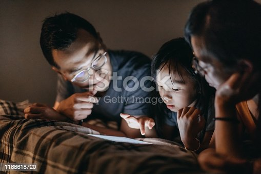 Parents and daughter lying on bed at home and using digital tablet before sleeping