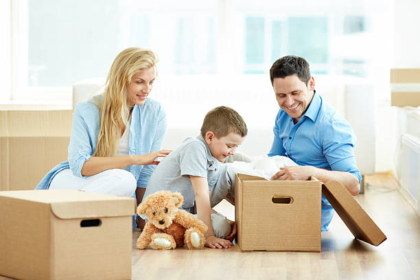 family moving house - happy mom packing some toys stock photos and pictures