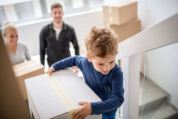 Family moving into new building Young heterosexual couple with their son carrying boxes through their new apartment building. model home stock pictures, royalty-free photos & images
