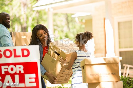 African descent family moving into a new home.  Mother, father and daughter.  Real estate sign.  Home in background.  Spring or summer season.