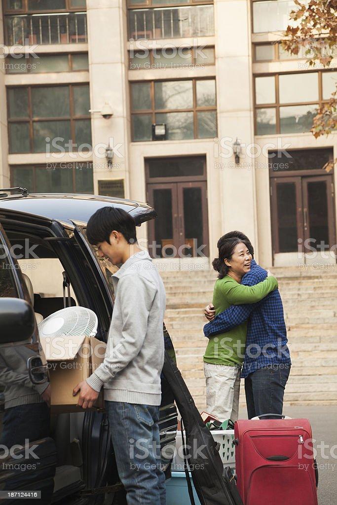 Família movendo seu filho em dormitório na college campus - foto de acervo