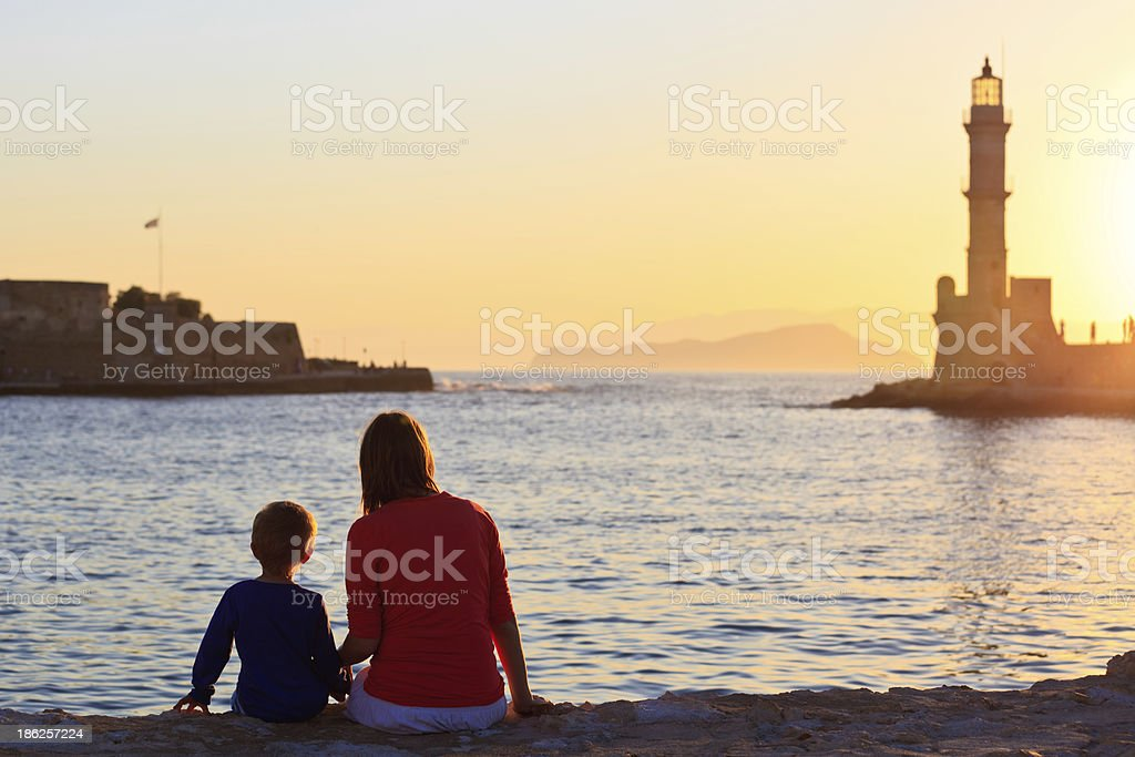 family near lighthouse in Greece at sunset stock photo