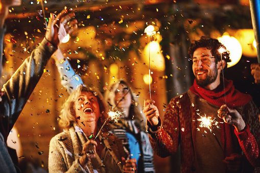 Family dancing and celebrating New Year's Eve outdoors. Confetti in focus.