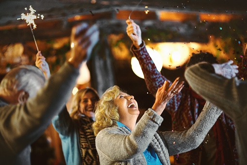 Family dancing at the back yard. Senior woman with arms raised looking at confetti that falling on her and laughing.