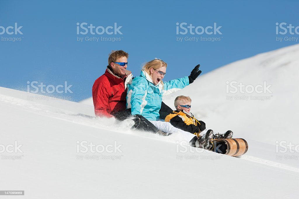 A family of 3 sledding in the Colorado snow royalty-free stock photo