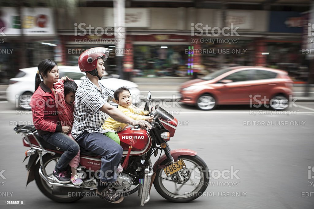 Family of 4 riding a motorcycle in China stock photo