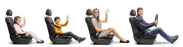 famille d'une mère, fils et fille dans les sièges de voiture agitant et un père retenant un volant avec des ceintures de sécurité - homme faire coucou voiture photos et images de collection