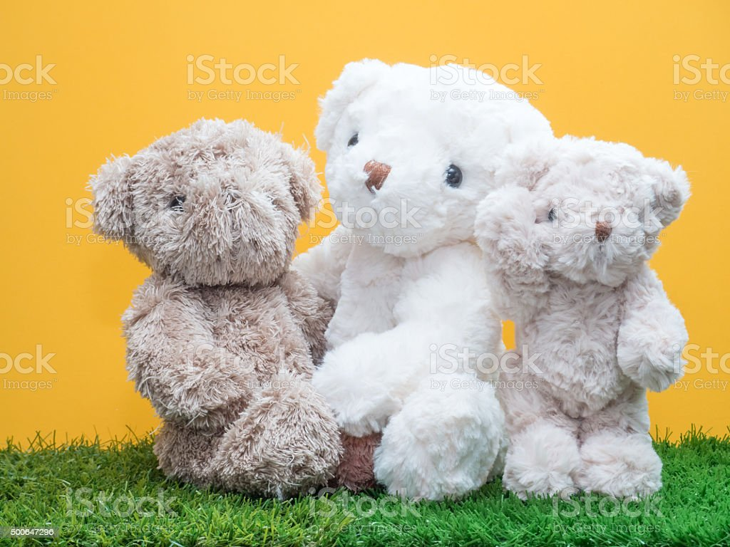 family of bear dolls sitting on artificial grass