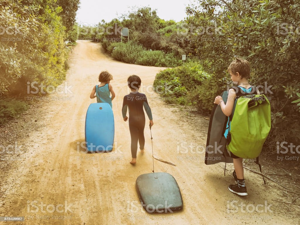 Family of boys walk to the beach together while carrying their boogie boards stock photo