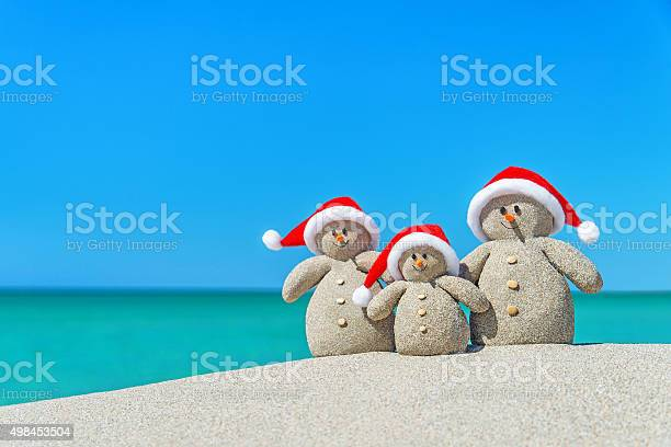 Photo of Family of Christmas Snowmen in santa hats at tropical beach.