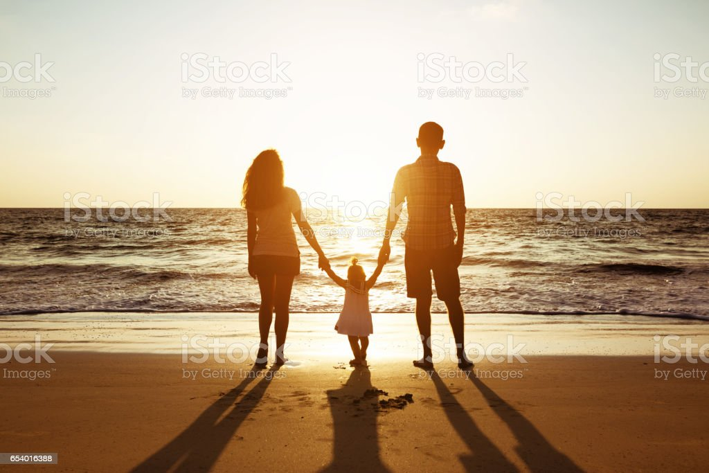 Family of father mother and daughter sunset sea silhouettes stock photo
