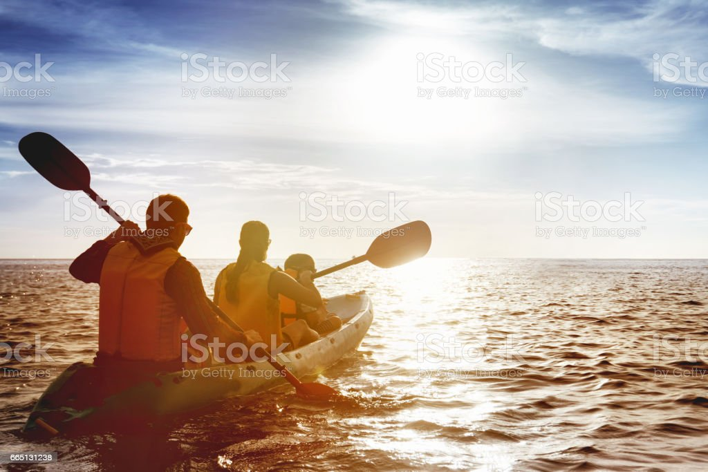 Family of father mother and son kayaking at sea sunset royalty-free stock photo
