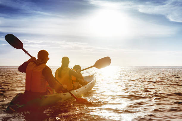 Family of father mother and son kayaking at sea sunset stock photo