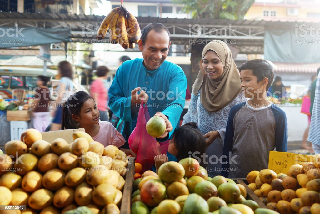 Family of five buying mangoes at market - Royalty-free 10-11 Years Stock Photo