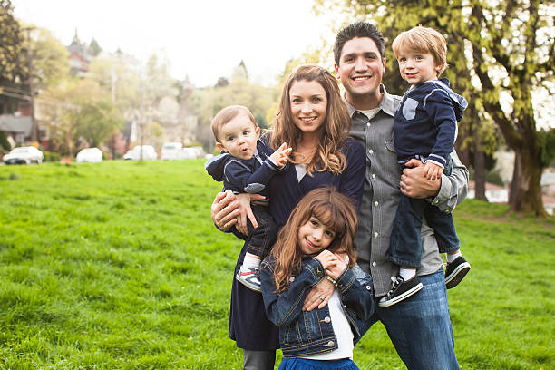 Family of five close together in park with copy space. stock photo