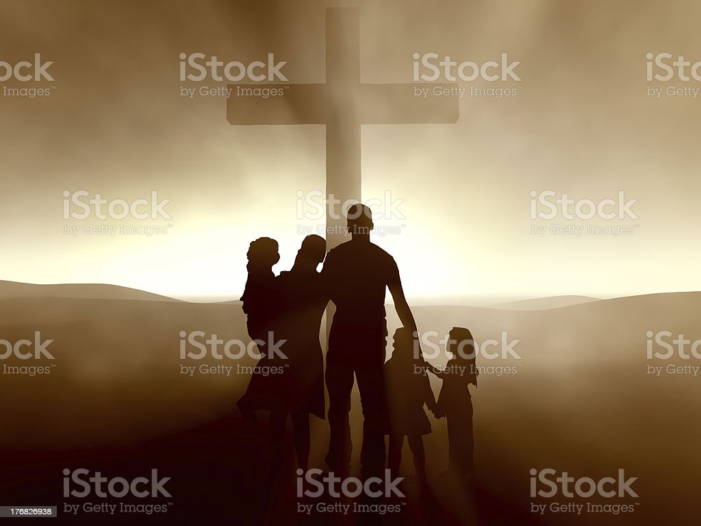 Family of five from behind looking at cross stock photo