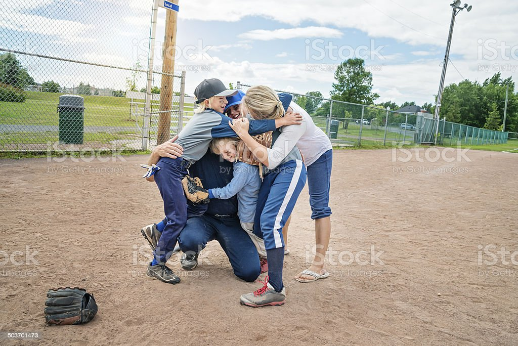 Family of five in a group hug after baseball game. royalty-free stock photo