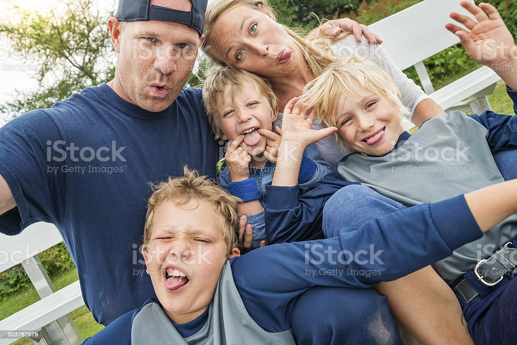 Family of five making faces for selfie after baseball game. stock photo